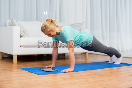 woman with tablet pc doing plank