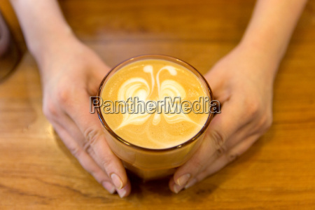 close up of hands with latte