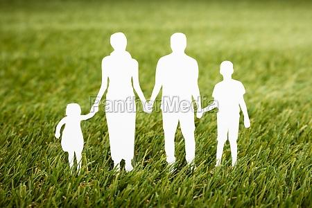 family papercut on grassy field