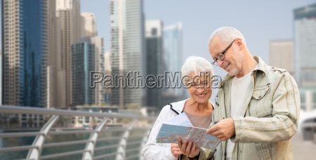 happy senior couple with map over