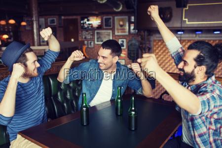 glueckliche maennliche freunde trinken bier an