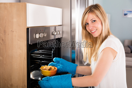 happy woman preparing food in oven