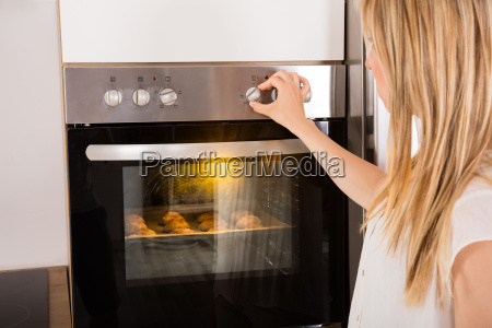 woman using oven for baking cookies