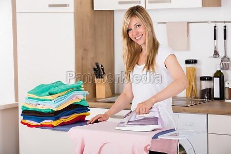 laechelnde frau buegeln kleider mit elektrischem