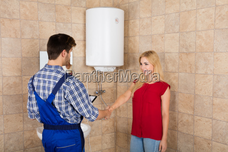 woman shaking hands with male plumber