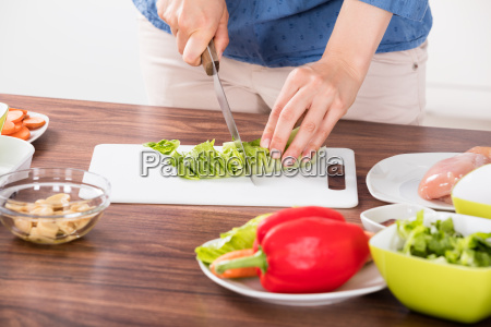 close up of woman cutting vegetable