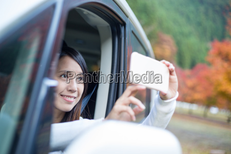 asian woman taking photo on cellphone