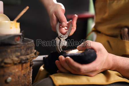 shoemaker nimmt manuell die schuhe in