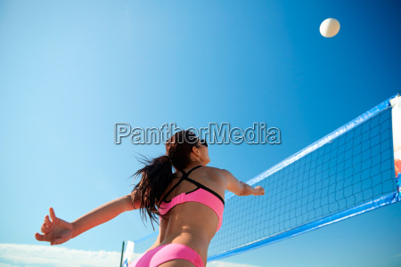 young woman with ball playing volleyball