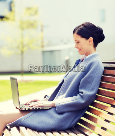 smiling business woman with laptop in