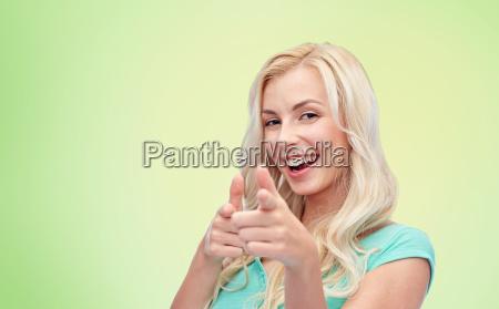 glueckliche junge frau zeigt finger zu