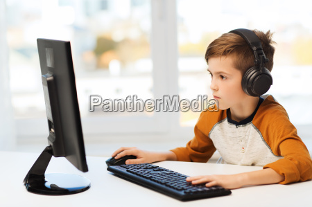 junge mit computer und kopfhoerer zu