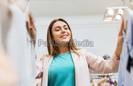 happy young woman choosing clothes in