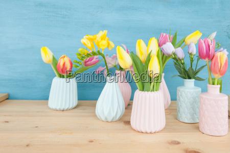 bunte fruehlingsblumen in kleinen vasen