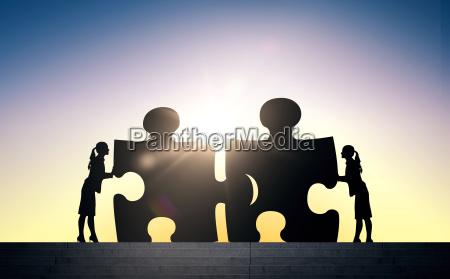 silhouette von zwei geschaeftsfrauen puzzle verbindungs