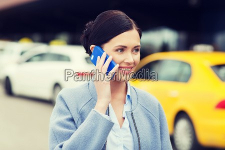 laechelnde frau mit smartphone ueber taxi