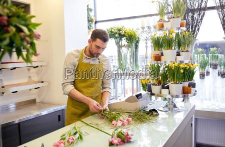 floristischer mann macht haufen im blumenladen