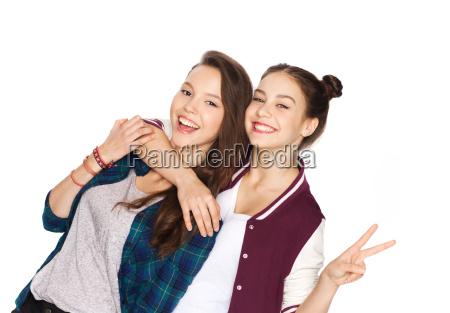 maedchen gluecklich teenager umarmen und friedenszeichen