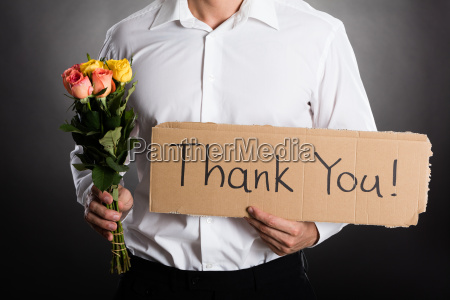 man holding roses and thank you