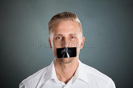 mann mit schwarzem klebeband ueber seinem