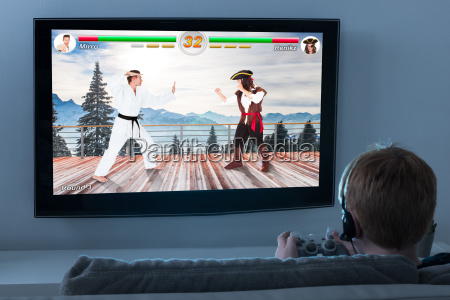 junge spielt aktion spiel auf fernsehen