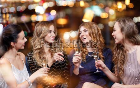 glueckliche frauen mit champagnerglaesern im nachtclub
