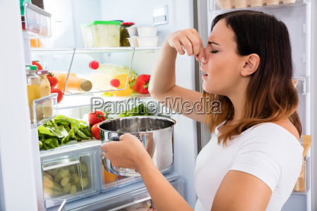 woman holding foul food near refrigerator