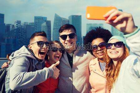 laechelnde freunde die selfie mit smartphone
