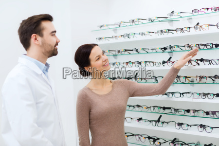 woman showing glasses to optician at