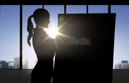 silhouette of woman with flipboard over