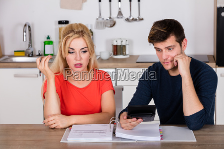 worried couple calculating their bills