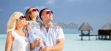 glueckliche familie ueber tropischem strand mit