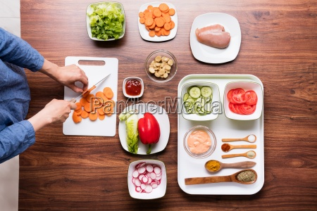 woman cutting vegetable on chopping board