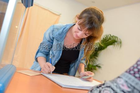 junge glueckliche geschaeftsfrau schriftlich notizen im