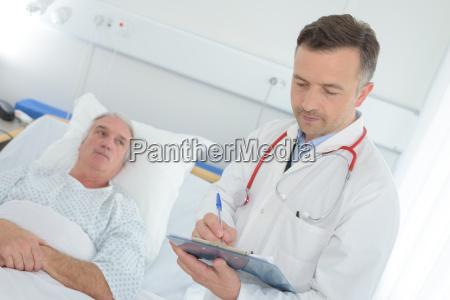 arzt mit klemmbrett besuch senior patient