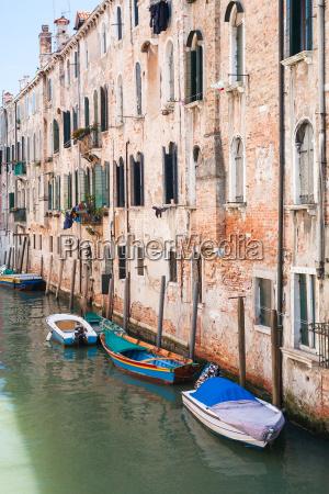 boats near shabby urban house in
