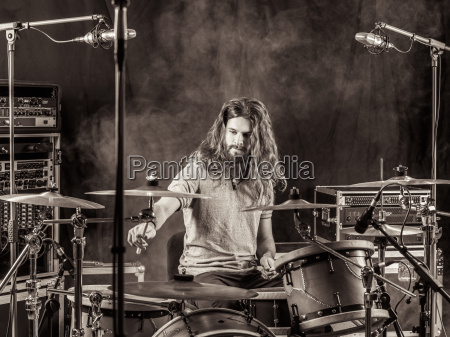 man with long hair playing drums