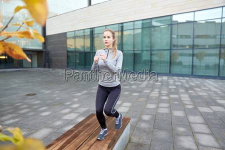 woman making step exercise on city