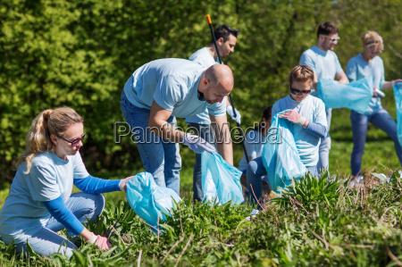 freiwillige mit muellsaecken reinigung park bereich