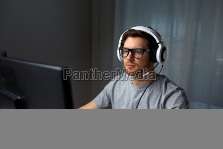 man in headset playing computer video