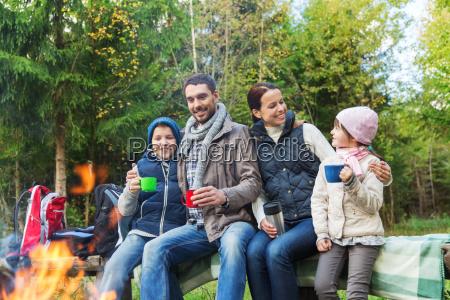 glueckliche familie auf bank am lagerfeuer
