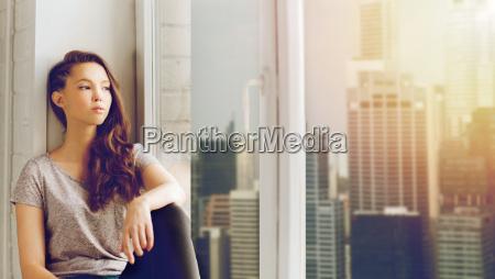 sad pretty teenage girl sitting on