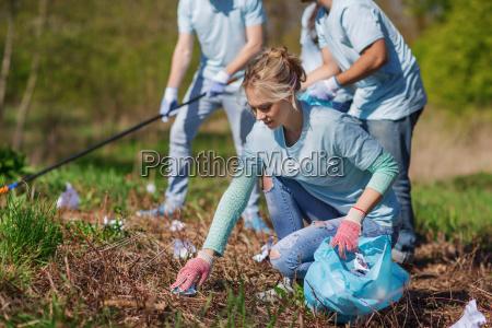 freiwillige mit muellsaecken reinigung parkbereich