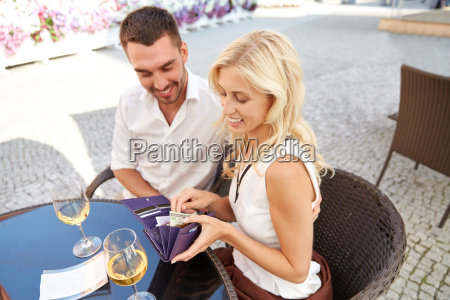 happy couple with wallet paying bill