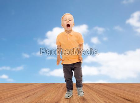 happy little boy shouting or sneezing