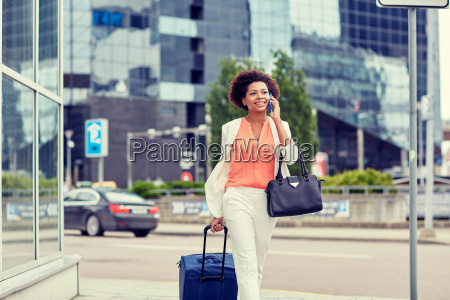 happy woman with travel bag calling