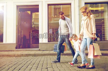 glueckliche familie mit kind und einkaufstueten