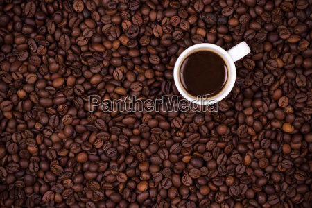coffee beans background with white cup