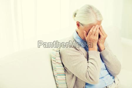 aeltere frau die unter kopfschmerzen oder