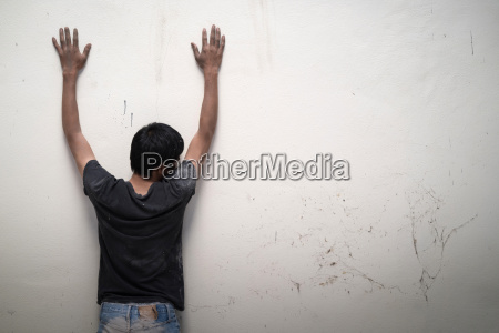 man show hands up facing the